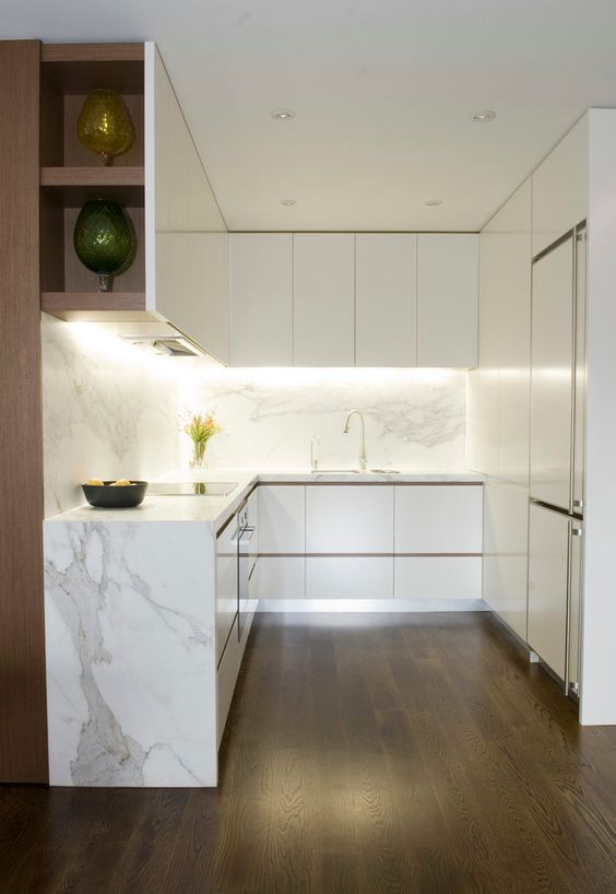 a refined minimalist kitchen with sleek white cabinets, a white marble backsplash and waterfall countertop, built-in lights and open storage compartments