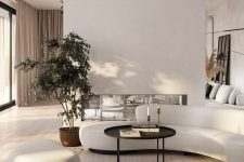 a refined minimalist living room in white, with a built-in fireplace and a curved sofa and ottoman, a round black coffee table and a potted plant