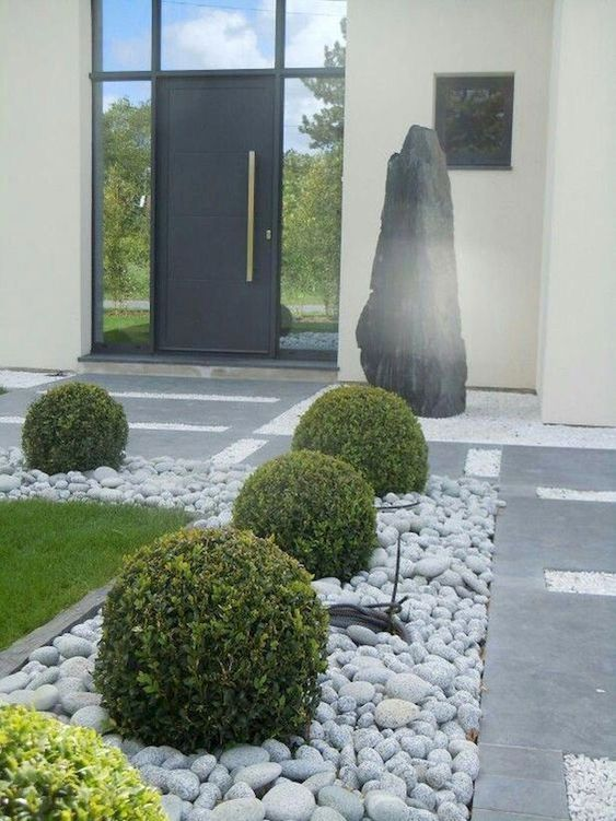 a refined modern front yard with stone tiles and rocks, with grass and elegant greenery balls looks chic and ultimate and inspires