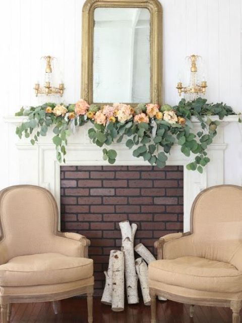 a refined summer mantel with greenery and pastel blooms, with a mirror in a gilded frame and a duo of candleholders is chic