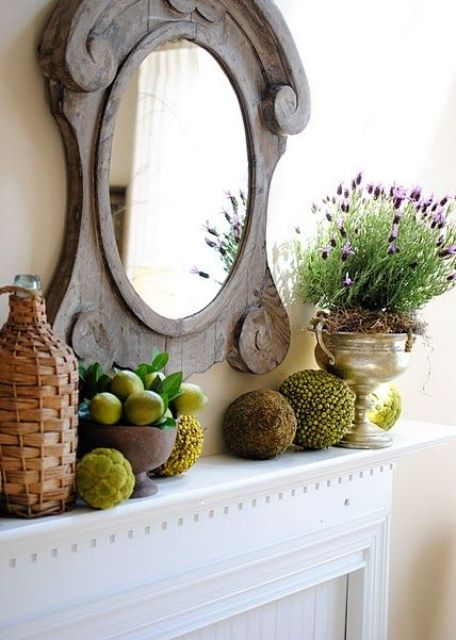 a refined vintage summer mantel with a mirror in a wooden frame, moss balls, lemons and greenery and lavender in a pot