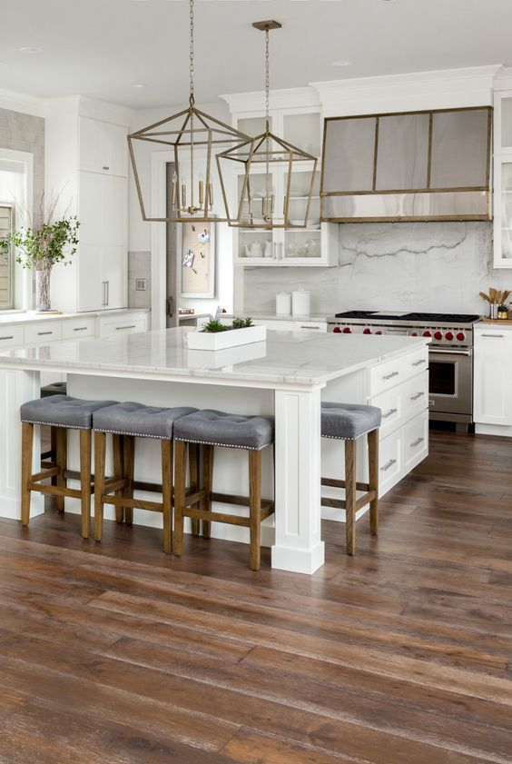 a refined white kitchen with chic cabinetry, a large kitchen island, metallic touches and beautiful hardwood floors