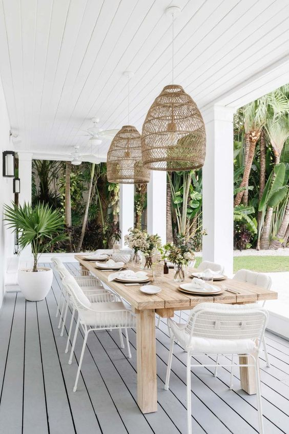 a relaxed tropical outdoor dining space with a stained wooden table, white chairs, pendant lamps and some greenery around