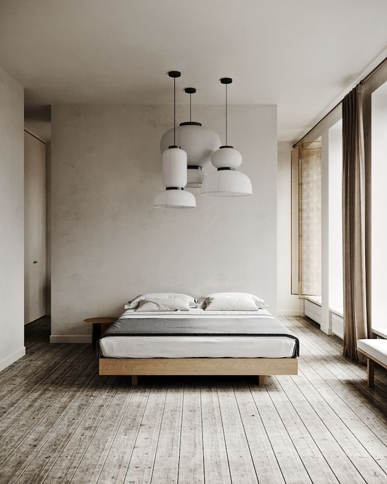 a relaxing minimalist bedroom with grey and neutral walls, a grey wooden floor, chic wooden furniture, pendant lamps and large windows