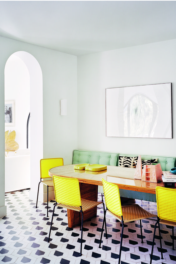 a retro-inspired dining space with light blue walls, a curved table, a green upholstered sofa, yellow chairs and a cool mosaic floor