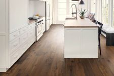 a rich-stained hardwood floor contrasts the white shaker-style kitchen cabinetry creating a bolder and cooler look