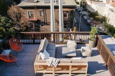 a rooftop terrace with a wooden deck, a sectional with poufs, bright chairs and a dining table plus metal chairs
