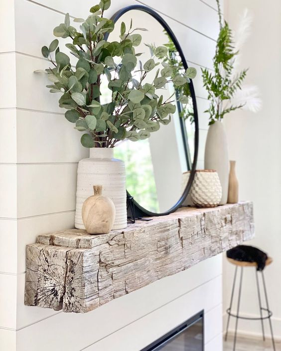 a rough wooden slab mantel with greenery arrangements in vases, elegant candleholders, a round mirror is a stylish idea