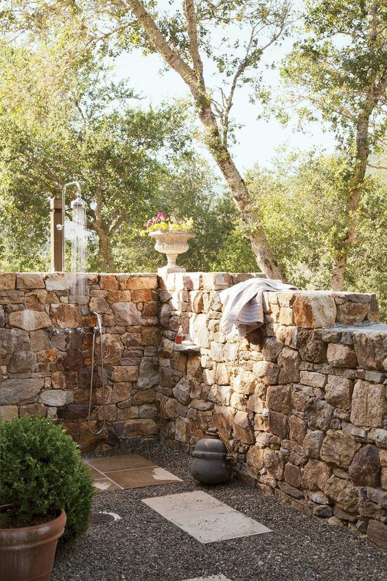 a rustic outdoor shower with stone walls, pebbles and tiles on the ground, potted greenery and blooms is a welcoming space