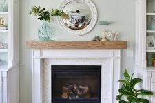 a simple and chic coastal mantel with corals and seashells, an aqua whale on a stand, an aqua bottle with greenery and a mirror reminding of a porthole