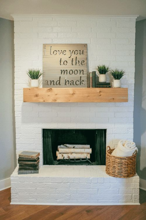 a simple and sleek summer mantel with potted grasses, a sign, some books and a basket with a blanket by its side