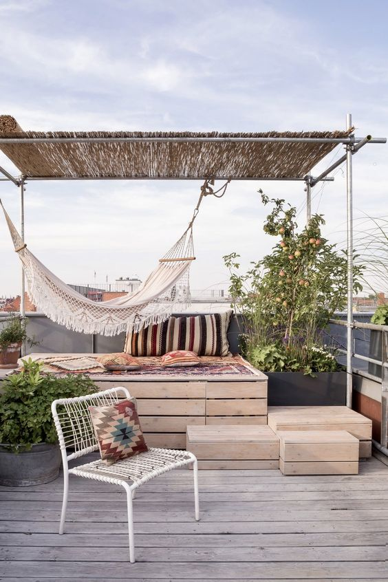 a simple boho rofotop terrace with a raised platform bed, a hammock, a woven chair, printed textiles and potted plants around