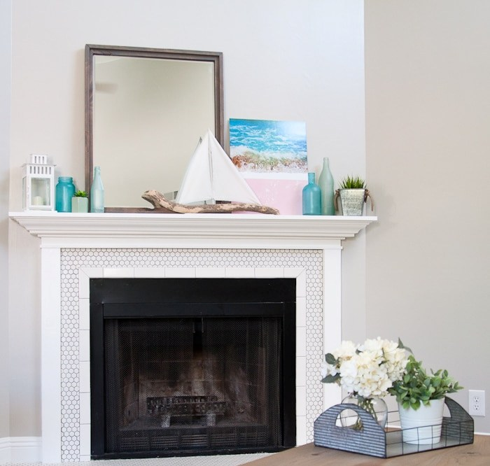 a simple coastal mantel with a driftwood boat, a mirror, some blue vases and bottles and a bold coast photo