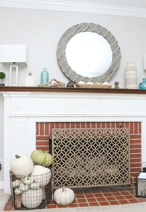 a simple coastal mantel with blue bottles and vases, with pumpkins in a plate, driftwood and a mirror that reminds of a porthole