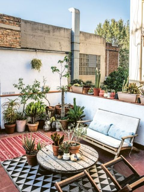 a simple modern summer patio with layered rugs, a round wooden table, some modern furniture and lots of potted plants and cacti