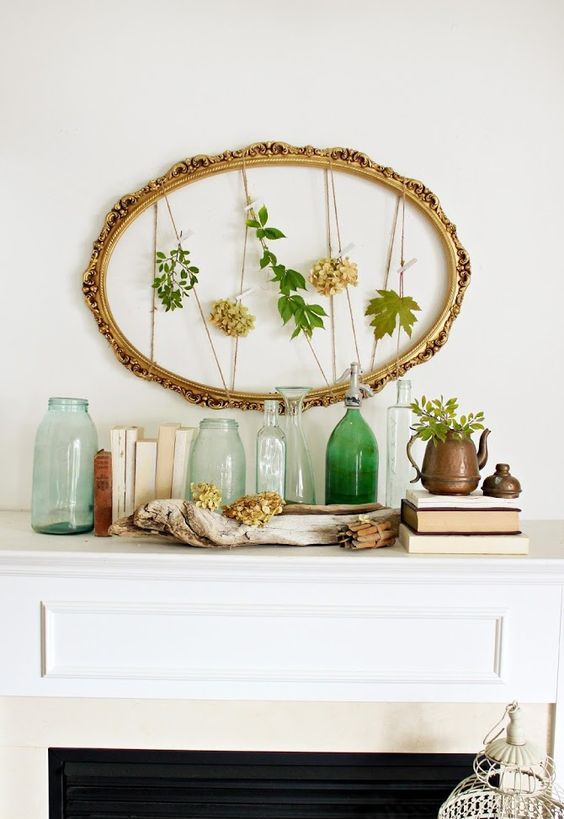 a simple summer mantel with a refined frame and leaves, with various bottles and jars, a vintage teapot with greenery