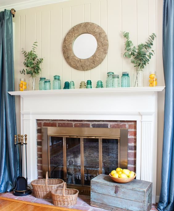 a simple summer mantel with lots of various jars and vases, with eucalyptus in vases, lemons in jars and a mirror in an ornated frame