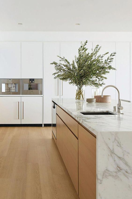 a sleek and refined minimalist kitchen with white cabinets and a waterfall countertop kitchen island, neutral fixtures and greenery