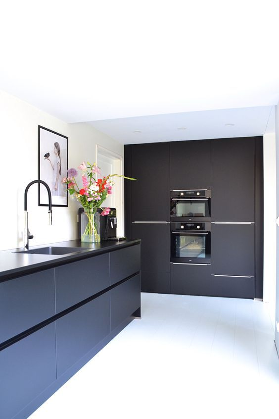 a sleek black kitchen with black countertops and fixtures, with artworks and some bright blooms is a chic and bold space