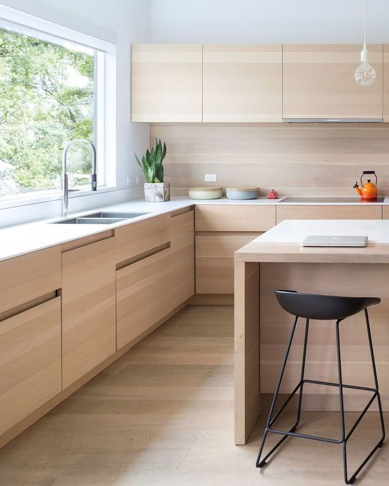 a sleek minimalist kitchen with light stained cabinets, a white countertop and a matching kitchen island plus black stools