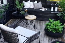 a small Scandinavian deck with a built-in black daybed, a white chair, mini round tables, potted plants and candle lanterns