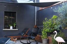a small Scandinavian deck with black loungers and chairs, printed pillows, potted greenery is welcoming and cool