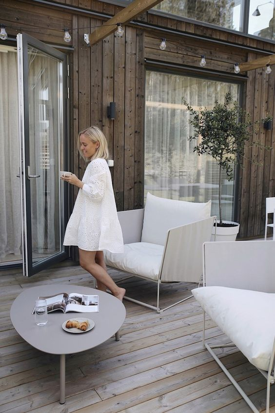a small and airy deck with large white chairs, a low grey coffee table and potted plants is a veyr chic and cool space