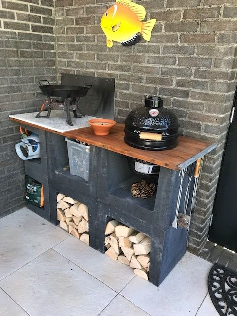 a small and comfy outdoor kitchen of black cinder blocks, with firewood, a grill and a cooker with a pan is amazing