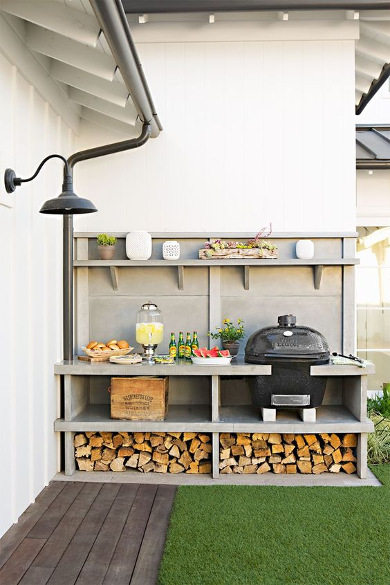 a small and cool outdoor kitchen with a open shelving unit, firewood, a crate, a grill and an open shelf for various stuff
