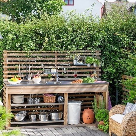 a small and cool outdoor kitchen with a planked screen used for attaching shelves, open shelves and a sink plus potted herbs