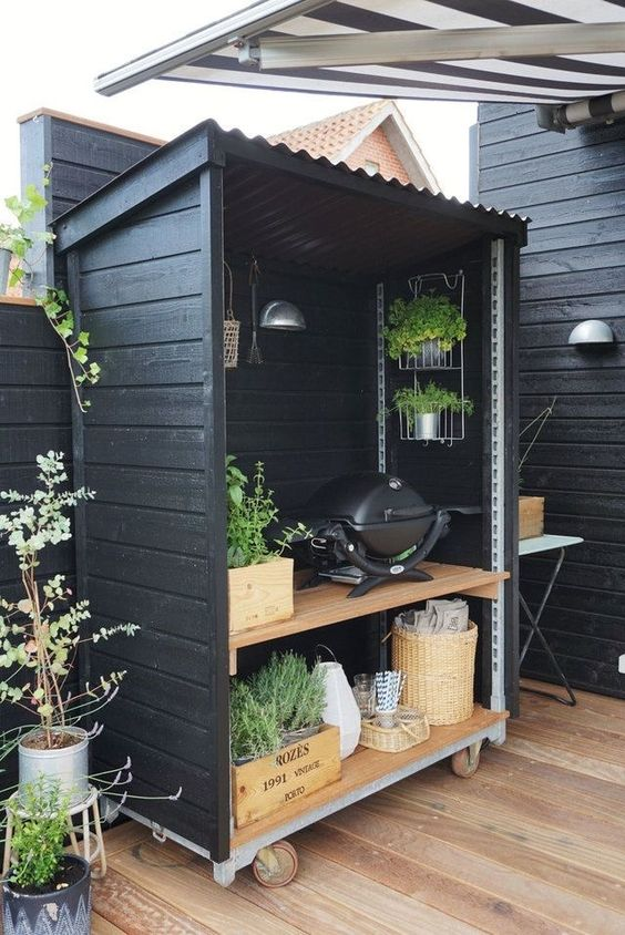 a small and cozy Scandinavian kitchen with a wooden unit covering shelves with a grill and some garden herbs is a genius idea