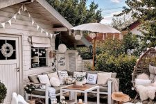 a small and cozy deck with a cool grey outdoor sofa, white loungers and a rattan chair, printed textules and potted plants and blooms