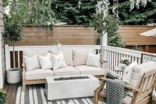a small and cozy deck with neutral furniture, a fireplace, potted plants and printed textiles everywhere is a chic space