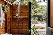 a cute outdoor shower with a wooden mat