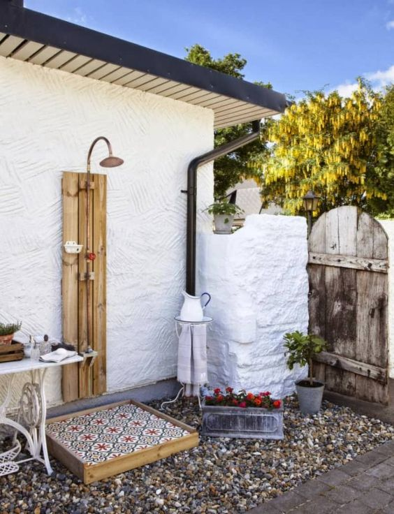 a small and cozy outdoor shower space with pebbles and a tiled shower surface, a jug and a vintage table, some potted blooms and greenery