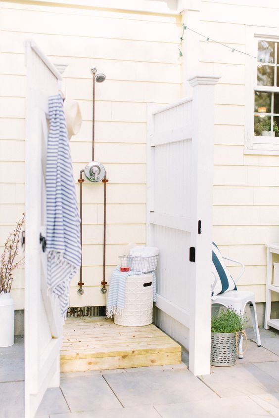 a small and cozy outdoor shower with planked wooden walls and a wooden bath mat plus printed textiles and a basket with eveyrthing necessary