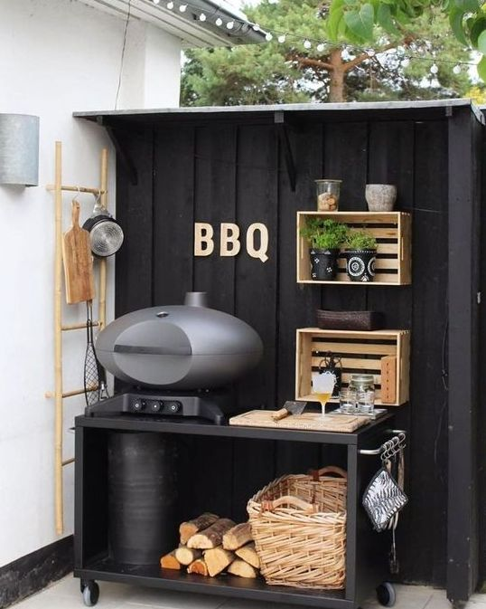 a small and cute outdoor kitchen of a black grill table with a basket and firewood, crate shelves attached to the wall and greenery