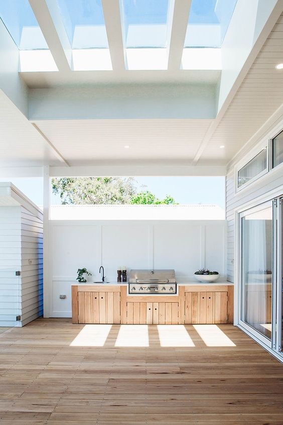 a small and elegant modern farmhouse outdoor kitchen with a planked unit that holds a grill, a sink and plants in a bowl