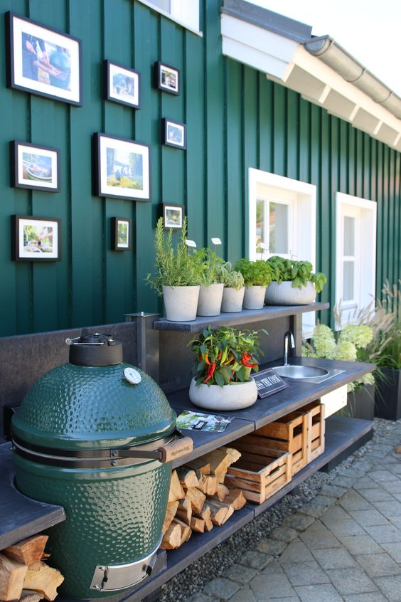 a small and functional outdoor kitchen with open shelves, a grill, a sink, somme firewood and crates for storage