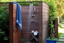 a small and private outdoor shower fully clad with stained wood and with walls, with a small stool and printed towels