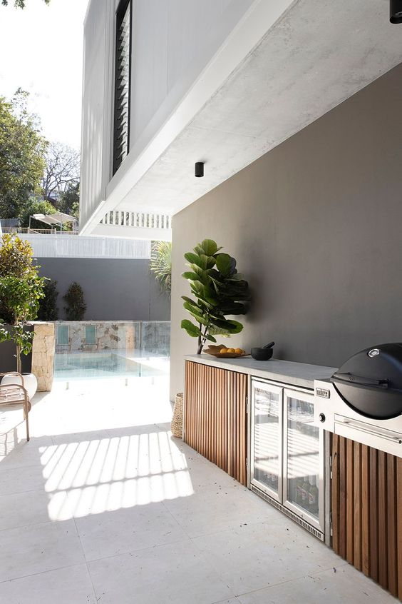a small and sleek contemporary outdoor kitchen with a concrete countertop and wooden cabinets, a drink cooler is a stylish space