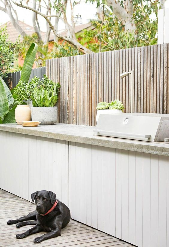 a small and sleek contemporary outdoor kitchen with a white planked cabinet and a concrete countertop, a grill, potted plants is very elegant