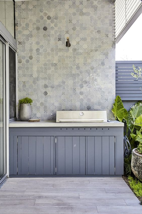 a small and sleek outdoor kitchen with grey planked cabinetry, a concrete countertop and a cooking surface, potted plants