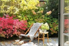 a small and welcoming deck with a lounger and a side table, pillows, bold plants and a tree that create a cool mood