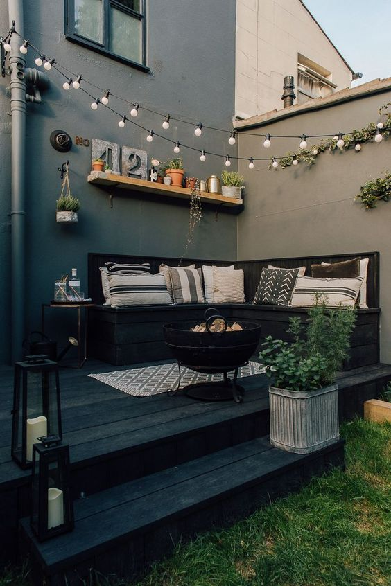 a small black deck with a built-in seat and printed pillows, string lights over the space, potted plants and candle lanterns