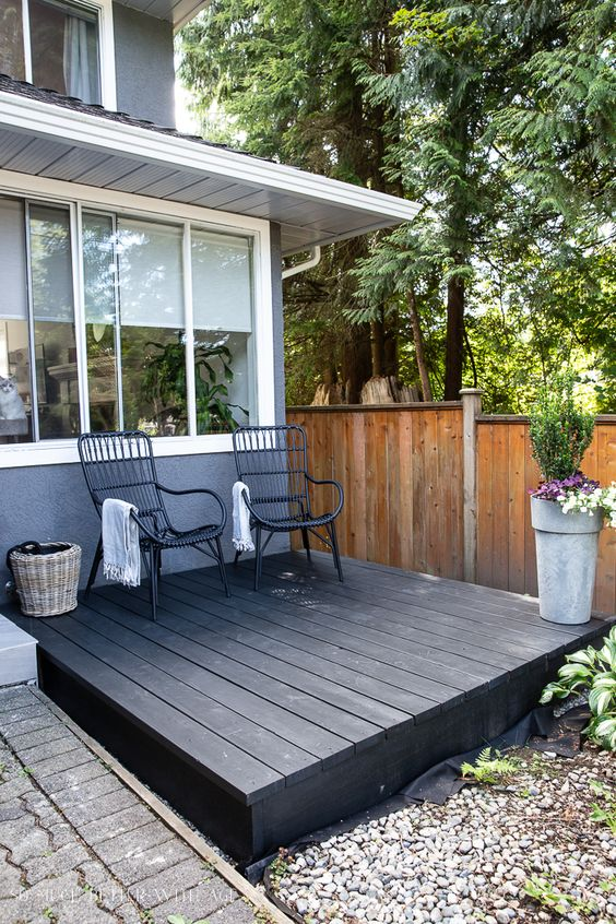 a small black deck with a couple of rattan chairs, potted plants and a basket is a very welcoming space to get some sunshine