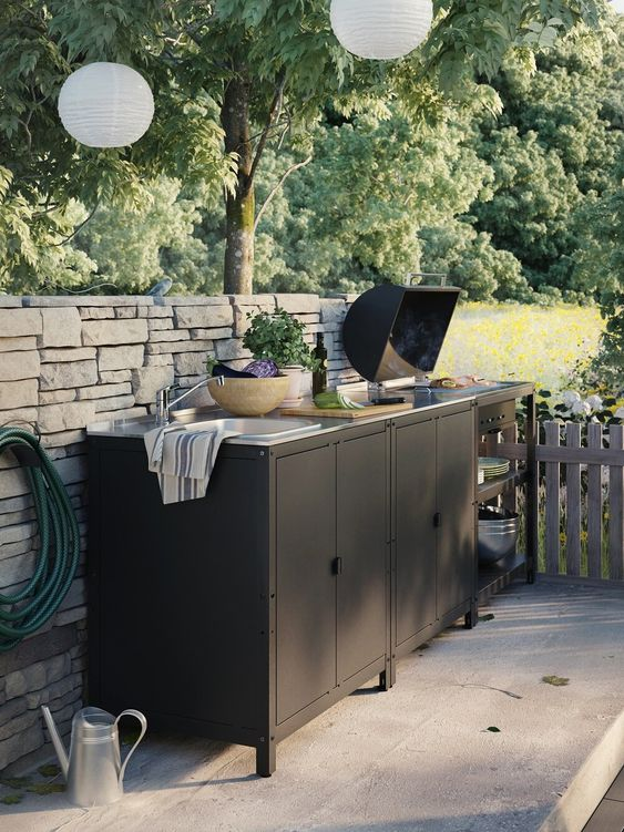 a small black kitchen by IKEA, of black metal cabinets and shelves that are very practical, a grill and a built-in sink