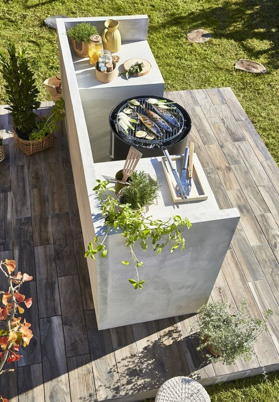 a small contemporary kitchen of concrete, with a grill and all the necessary stuff including potted herbs is lovely