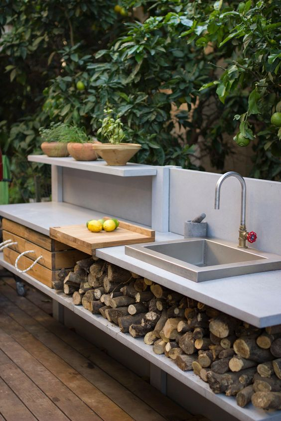 a small contemporary outdoor kitchen with an open shelving unit that stores firewod and a crate, with a built-in sink and potted herbs