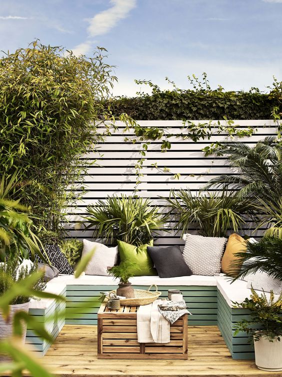 a small deck surrounded with greenery, with a green pallet daybed, a pallet coffee table and colorful pillows is welcoming